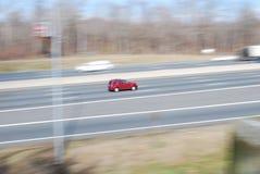 Beschleunigendes rotes Auto, das hinunter Landstraße hetzt stockfotos