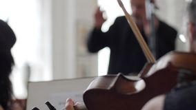 Beschleunigte Bewegung, Violinist spielt auf Geige vor einem musikalischen Stand auf Hintergrundleiter stock footage
