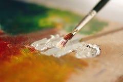 Beschmutzte Bürste mischt weiße Ölfarbe auf einer Palette lizenzfreie stockfotos