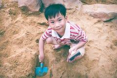 Beschneidungspfad eingeschlossen Der entzückende asiatische Junge hat Spaß grabend im Sand auf einer SU Lizenzfreie Stockbilder