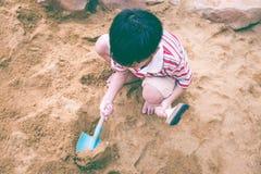 Beschneidungspfad eingeschlossen Der entzückende asiatische Junge hat Spaß grabend im Sand auf einer SU Stockbilder