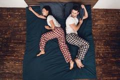 Beschneidungspfad eingeschlossen Die junge schlafende Frau, die über Bett ausgebreitet wird und hindert verblüfften Mann am Schla stockfotos