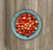Beschneidungspfad eingeschlossen Reife und geschmackvolle Kirschen auf einem hölzernen Hintergrund Lizenzfreie Stockbilder