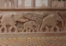 Beschreibung der Elefantfamilie auf rotem Stein durch das Schnitzen Lizenzfreie Stockbilder