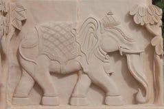 Beschreibung von Elefanten auf rotem Stein durch das Schnitzen Lizenzfreies Stockfoto