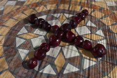 Beschriften Sie X, das mit cherrys gemacht wird, um einen Buchstaben des Alphabetes mit Früchten zu bilden Lizenzfreie Stockfotografie