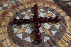 Beschriften Sie X, das mit cherrys gemacht wird, um einen Buchstaben des Alphabetes mit Früchten zu bilden Stockfoto