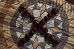 Beschriften Sie X, das mit cherrys gemacht wird, um einen Buchstaben des Alphabetes mit Früchten zu bilden Stockfotografie