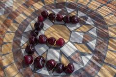 Beschriften Sie E, das mit cherrys gemacht wird, um einen Buchstaben des Alphabetes mit Früchten zu bilden Stockfoto