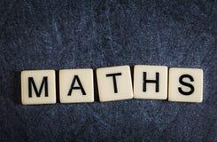 Beschriften Sie Fliesen auf schwarzem Schieferhintergrund-Rechtschreibung Mathe stockbilder