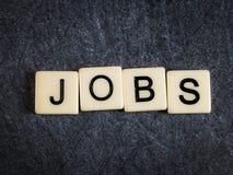Beschriften Sie Fliesen auf schwarzen Schieferhintergrund-Rechtschreibung Jobs lizenzfreies stockfoto