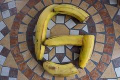Beschriften Sie G, der mit Bananen gemacht wird, um einen Buchstaben des Alphabetes mit Früchten zu bilden Stockfotografie
