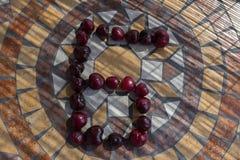 Beschriften Sie G, der mit cherrys gemacht wird, um einen Buchstaben des Alphabetes mit Früchten zu bilden Stockbilder