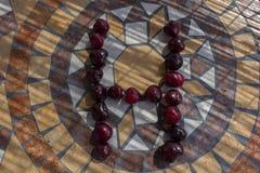 Beschriften Sie H, das mit cherrys gemacht wird, um einen Buchstaben des Alphabetes mit Früchten zu bilden Stockfotografie