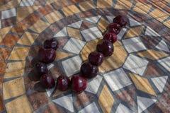 Beschriften Sie J, das mit cherrys gemacht wird, um einen Buchstaben des Alphabetes mit Früchten zu bilden Stockfotografie