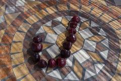 Beschriften Sie J, das mit cherrys gemacht wird, um einen Buchstaben des Alphabetes mit Früchten zu bilden Lizenzfreies Stockfoto