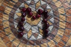 Beschriften Sie M, das mit cherrys gemacht wird, um einen Buchstaben des Alphabetes mit Früchten zu bilden Stockfotos