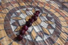 Beschriften Sie mich machte mit cherrys, um einen Buchstaben des Alphabetes mit Früchten zu bilden Stockfotografie