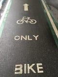 Beschriften Sie nur Fahrrad und Fahrrad auf nasser schwarzer Straße Lizenzfreie Stockfotos