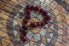 Beschriften Sie P, das mit cherrys gemacht wird, um einen Buchstaben des Alphabetes mit Früchten zu bilden Stockfoto