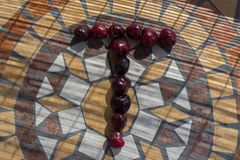 Beschriften Sie T, die mit cherrys gemacht wird, um einen Buchstaben des Alphabetes mit Früchten zu bilden Stockbilder