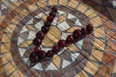 Beschriften Sie V, das mit cherrys gemacht wird, um einen Buchstaben des Alphabetes mit Früchten zu bilden Stockfotos