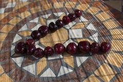 Beschriften Sie V, das mit cherrys gemacht wird, um einen Buchstaben des Alphabetes mit Früchten zu bilden Lizenzfreies Stockbild