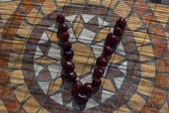 Beschriften Sie V, das mit cherrys gemacht wird, um einen Buchstaben des Alphabetes mit Früchten zu bilden Stockbild