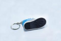 Beschuhen Sie Sohlen blauen sneeaker Schlüsselanhängers, der auf weißem backgrou lokalisiert wird Lizenzfreie Stockfotografie