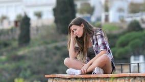 Beschwerdec$sitzen der traurigen Jugendlichen auf einer Leiste stock video