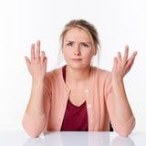 Beschwerende junge blonde Frau, die mit den verärgerten Händen oben sich ausdrückt Lizenzfreies Stockfoto