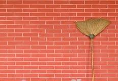 Besen auf Backsteinmauer Stockbild