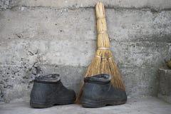 Besen und alte Stiefel stehen auf dem Boden Stockfotografie