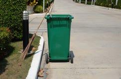 Besen und grüner Behälter gesetzt nahe bei dem Straßenrandweg stockbilder