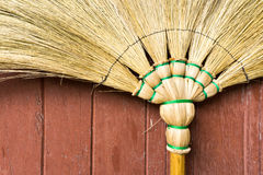 Besenstiel gelegt auf eine Brown-Holztür Lizenzfreies Stockbild