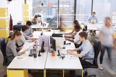 Besetzen Sie das Gehen durch einen beschäftigten Bürogroßraum, Seitenansicht mit Personal lizenzfreie stockfotografie