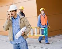 Besetzte Bauarbeiter, die Strichleiter tragen Stockfotografie