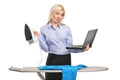 Besetzte Geschäftsfrau, die an einem Laptop bügelt und arbeitet lizenzfreies stockfoto