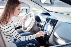 Besetzte interessierte Frau, die im Auto hält rührendes Bedienfeld sitzt stockfoto
