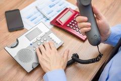 Besetzter Geschäftsmann mit Bericht ruft Kunden für explanat an Lizenzfreie Stockfotografie