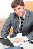 Besetzter Geschäftsmann mit Laptop, Mobiltelefon und Becher Stockbilder
