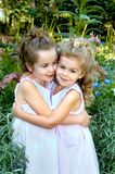 Besides my Sister. Two young sisters embrace in a garden.  Flowers and sunshine.  Both are dressed in light pink sleeveless dresses Royalty Free Stock Photos