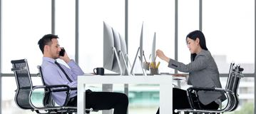 Besinessman and businesswoman working together in modern office. royalty free stock photography