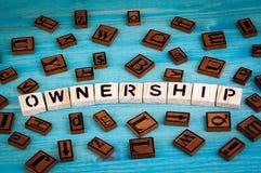 Besitzwort geschrieben auf hölzernen Block Hölzernes Alphabet auf einem blauen Hintergrund Lizenzfreie Stockfotografie