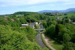 Beskåda över by för gröna kullar Arkivbild