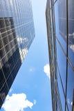 Beskåda anseendet mellan två högväxta glass skyskrapor som ser raka upp på både byggnader som reflekterar sig och himlen - perspe Arkivfoton