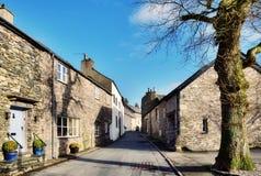Beskåda av en gata i Cartmel, Cumbria med treen Royaltyfri Foto