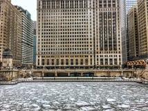 Beskåda Chicago riverwalk över ett djupfrysta Chicago River och snöflingor under tungt morgonsnöfall fotografering för bildbyråer
