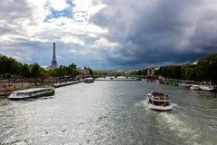 Beskåda fartygridningen på Seinet River med Eiffeltorn i bakgrunden, med dramatiska himlar över staden paris Arkivfoto