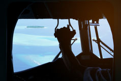 Beskåda från inre sjöflygplancockpiten som ut ser till Maldiverna små öar Arkivbild